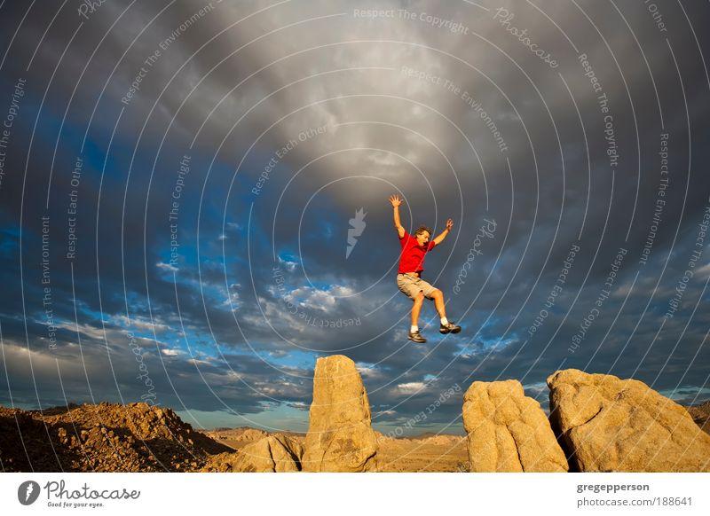Kletterer auf dem Gipfel. Abenteuer Freiheit wandern Klettern Bergsteigen Mann Erwachsene 1 Mensch Gewitterwolken Felsen Wanderschuhe fliegen springen hoch