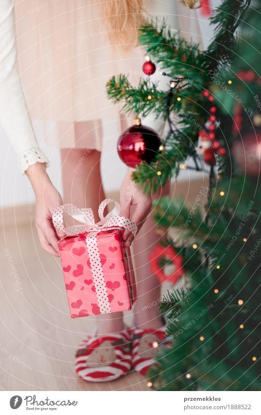 Nahaufnahme des Mädchens Weihnachtsgeschenk von unter einem Baum erhalten Lifestyle Feste & Feiern Weihnachten & Advent Kind Mensch 1 8-13 Jahre Kindheit Kleid
