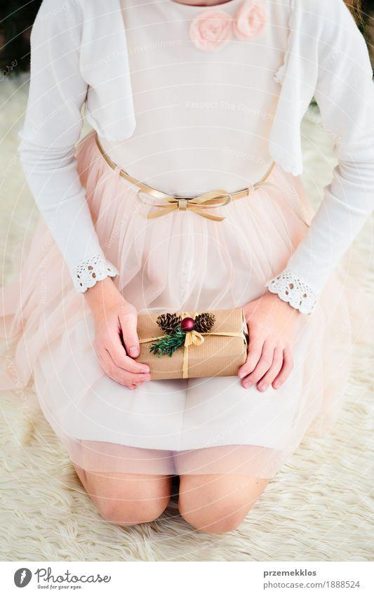 Mädchen, das Weihnachtsgeschenk hält und auf einem Teppich sitzt Lifestyle Feste & Feiern Weihnachten & Advent Kind Mensch 1 8-13 Jahre Kindheit Kleid rosa rot
