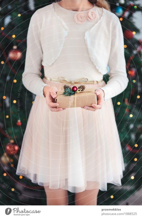Mädchen, das Weihnachtsgeschenk und -stellung vor Baum hält Lifestyle Feste & Feiern Weihnachten & Advent Kind Mensch 1 8-13 Jahre Kindheit Kleid rosa rot