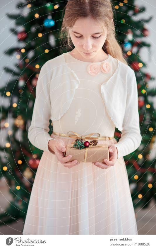 Mädchen, das Weihnachtsgeschenk und -stellung vor Baum hält Lifestyle Feste & Feiern Weihnachten & Advent Kind Mensch 1 8-13 Jahre Kindheit Kleid blond rosa