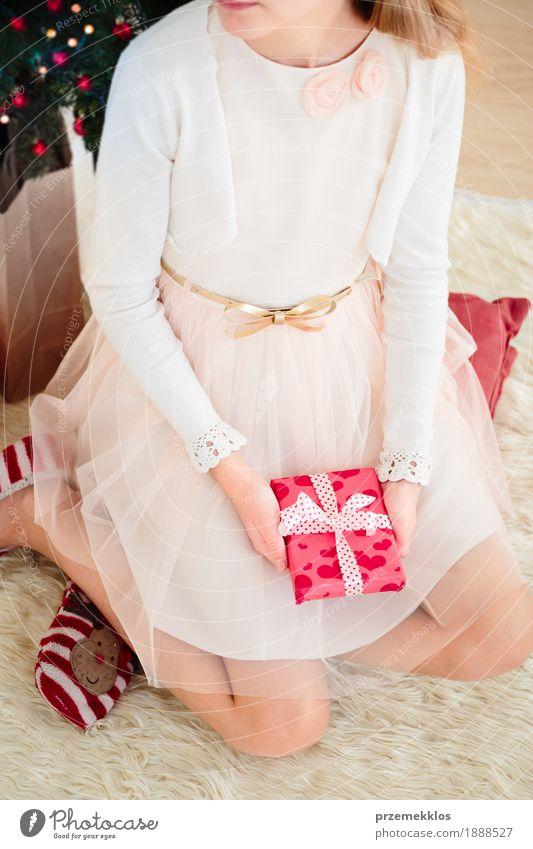 Tragendes Kleid des Mädchens, welches das Weihnachtsgeschenk sitzt auf einem Teppich hält Lifestyle Dekoration & Verzierung Feste & Feiern Weihnachten & Advent