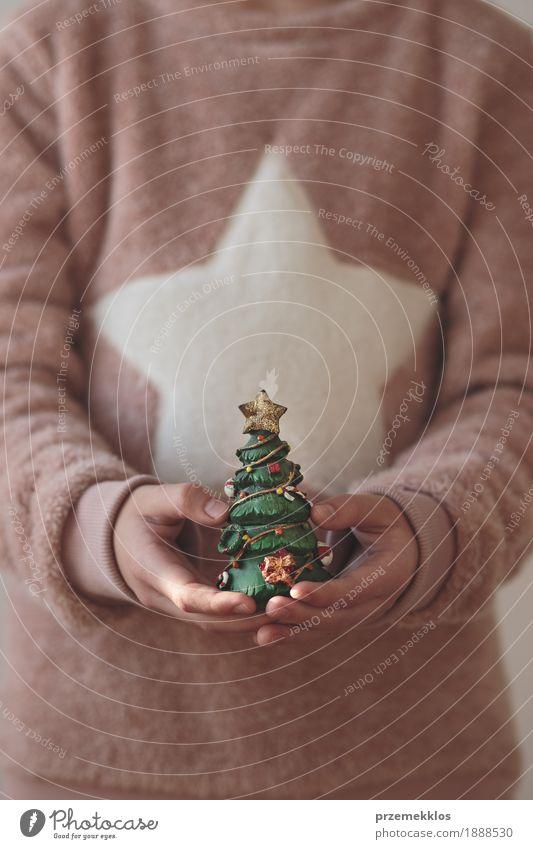 Mädchen, das die warme Strickjacke hält Weihnachtsbaumfigürchen trägt Lifestyle Feste & Feiern Weihnachten & Advent Mensch Jugendliche 1 8-13 Jahre Kind