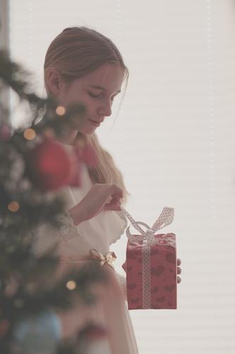 Mädchen, welches das Weihnachtsgeschenk steht hinter einem Baum auspackt Lifestyle Feste & Feiern Weihnachten & Advent Kind Mensch 1 8-13 Jahre Kindheit Kleid