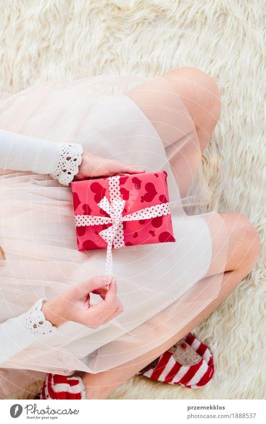 Mädchen, das Weihnachtsgeschenk auf Beinen hält und auf einem Teppich sitzt Lifestyle Feste & Feiern Weihnachten & Advent Kind Mensch Hand 1 8-13 Jahre Kindheit