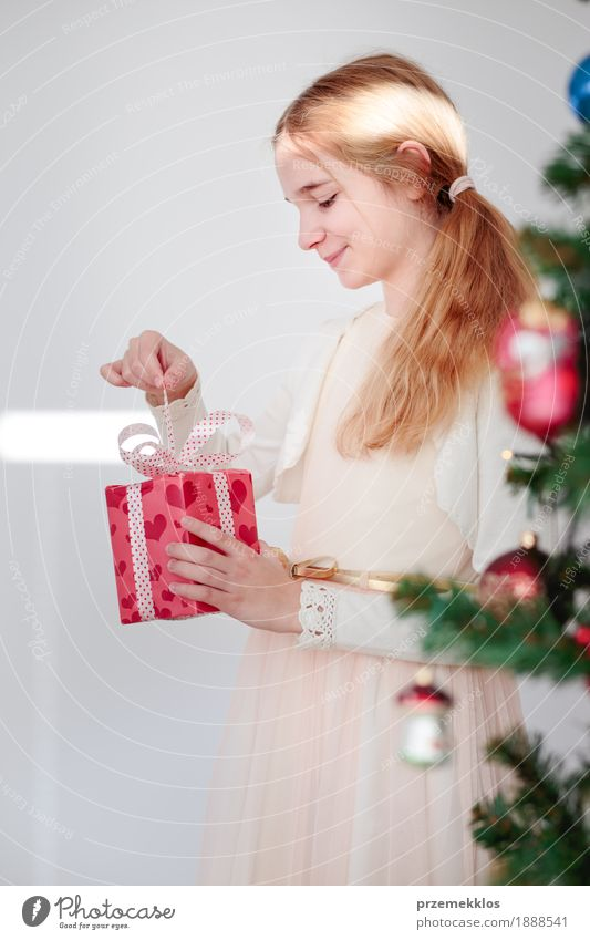 Glückliches Mädchen, welches das Weihnachtsgeschenk steht hinter einem Baum auspackt Lifestyle Feste & Feiern Weihnachten & Advent Kind Mensch 1 8-13 Jahre