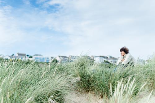 Frau sitzt in den Dünen und schaut nach vorn harmonisch Wohlgefühl Zufriedenheit Erholung ruhig Freizeit & Hobby Ferien & Urlaub & Reisen Freiheit Sommerurlaub