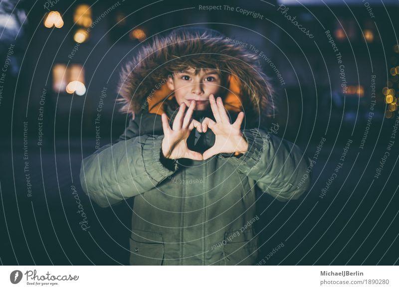 Junge zeigt Herz mit Händen, in Winterkleidung in Stadtumgebung Kind Mensch maskulin Kindheit Finger 1 3-8 Jahre Liebe Zeichen Symbole & Metaphern dunkel Jacke