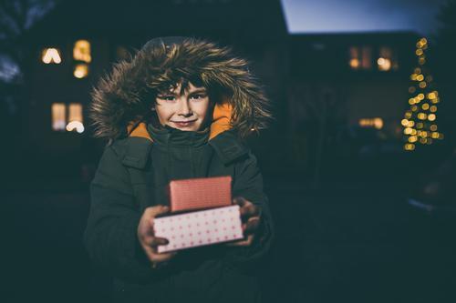 Junge mit Geschenken zu Weihnachten, Bokeh Lichter Winter Weihnachten & Advent Kind Mensch maskulin Kindheit 1 3-8 Jahre Freude Zufriedenheit Lebensfreude Paket