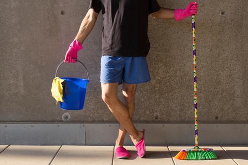 Ein Hausmann in rosaroten Hausschuhen und Putzutensilien Sommer maskulin Mann Erwachsene Körper 1 Mensch 30-45 Jahre Mauer Wand Besen Eimer Handschuhe Putztuch