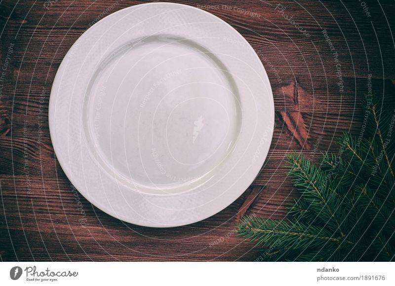Weiße leere Platte mit einer grünen Niederlassung der Fichte Abendessen Geschirr Teller Tisch Küche Weihnachten & Advent Silvester u. Neujahr Holz alt oben