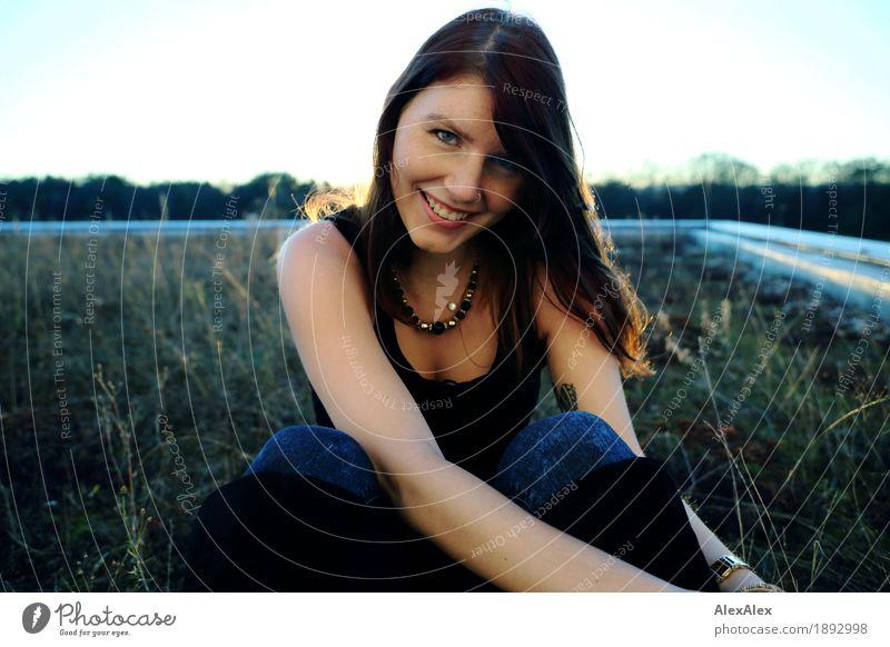 Junge Frau mit Sommersprossen sitzt im Abendlicht auf einem hohen Flachdach und lächelt in die Kamera Lifestyle schön Dachgarten Jugendliche Gesicht 18-30 Jahre
