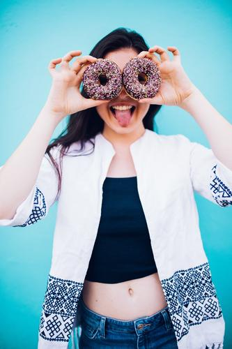 Mädchen, das Schokoladenschaumgummiringe vor ihrem Gesicht hält Lebensmittel Kuchen Dessert Süßwaren Essen Fastfood Lifestyle Freude Mensch Junge Frau