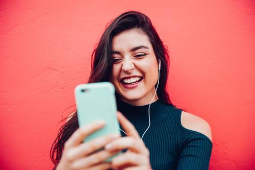 Junges glückliches Frauenvideo, das mit intelligentem Telefon plaudert Lifestyle Freude Musik Handy Headset MP3-Player PDA Technik & Technologie