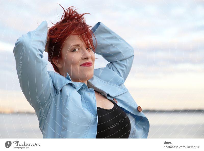 Anastasia feminin Frau Erwachsene 1 Mensch Küste Flussufer T-Shirt Mantel rothaarig langhaarig beobachten festhalten Lächeln Blick warten frisch schön Glück