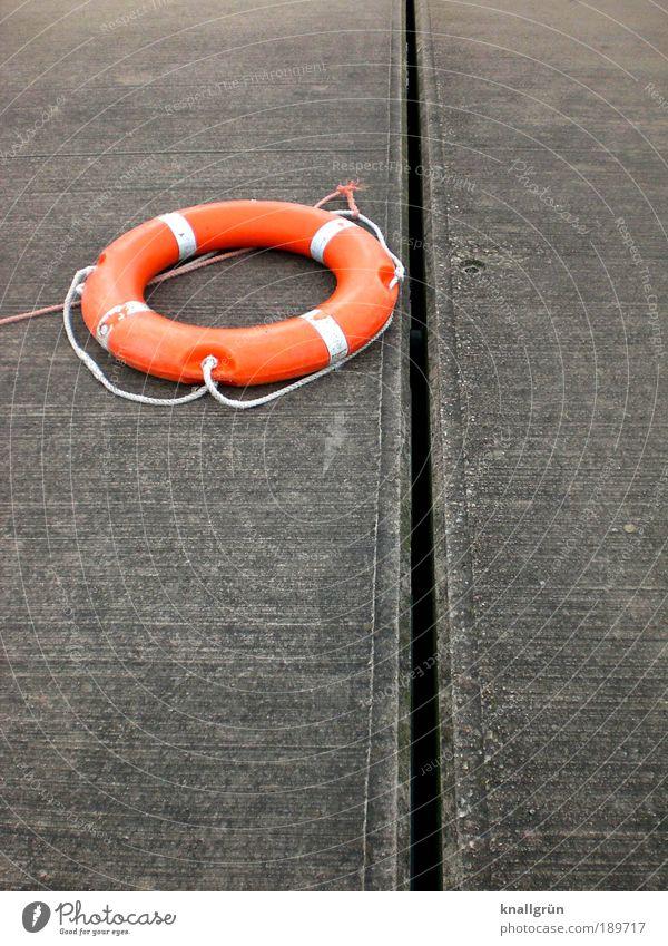 Rettungsring gebrauchen liegen rund grau weiß Tatkraft Sicherheit Angst bedrohlich Hilfsbereitschaft Hoffnung Überleben orange auf dem trockenen Maritim