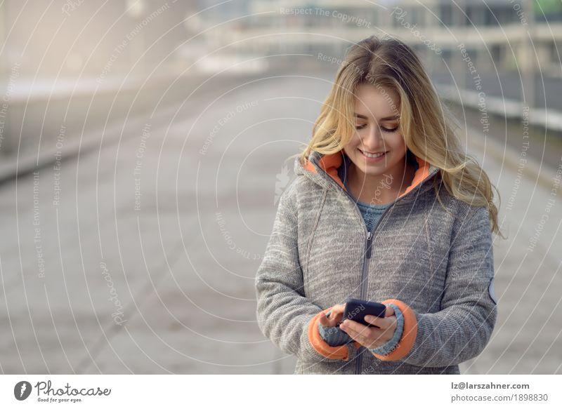 Junge Frau mit dem Handy gehend eine Stadtstraße Lifestyle schön lesen Ferien & Urlaub & Reisen Winter Telefon PDA Technik & Technologie Erwachsene 1 Mensch