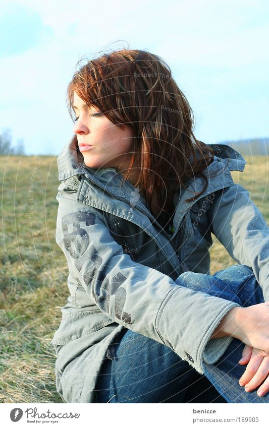 Wintersonne Frau Sonne Sonnenbad Jacke sitzen Erholung Zufriedenheit langhaarig Mantel Augen geschlossen schlafen Wiese Feld Natur natürlich Jugendliche Pause 1