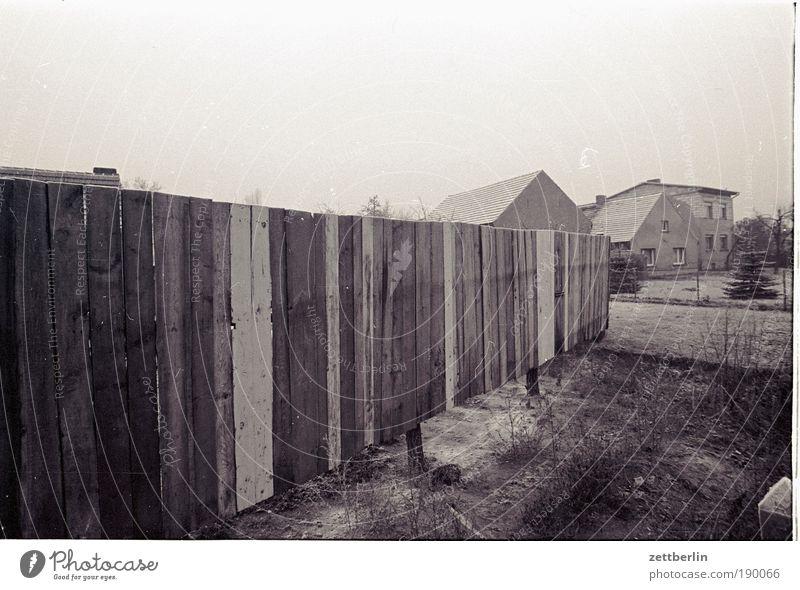 Bretterzaun Zaun staketenzaun Holz Holzbrett Grundstück Dorf Grenze trüb Traurigkeit trist