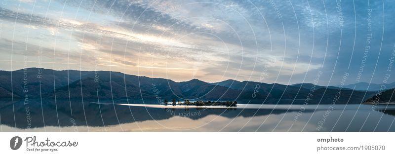 Weite Panoramalandschaft eines Bergsees mit einer kleinen Insel in der Mitte Winter Berge u. Gebirge Natur Landschaft Wasser Himmel Wolken Sonnenaufgang