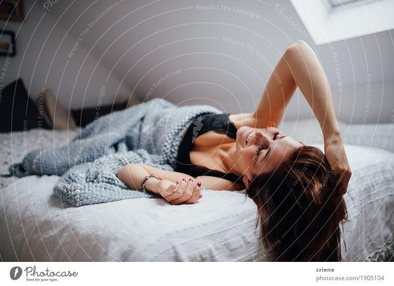 Das junge weibliche erwachsene Legen entspannt auf dem Bettlächeln Lifestyle Freude Glück ruhig Häusliches Leben Wohnung Haus Innenarchitektur Raum Schlafzimmer