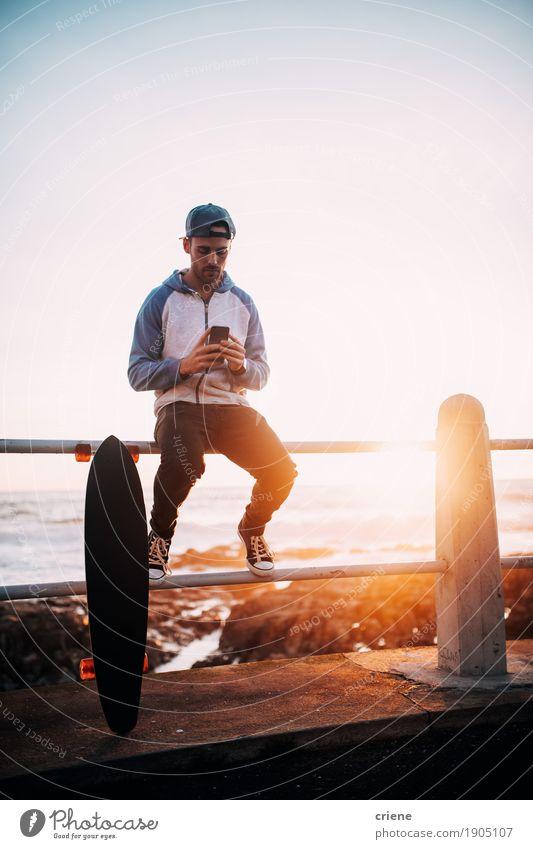 Junger erwachsener Mann, der auf dem Geländerbrowsen mit intelligentem Telefon sitzt Lifestyle sprechen Handy PDA Technik & Technologie Unterhaltungselektronik
