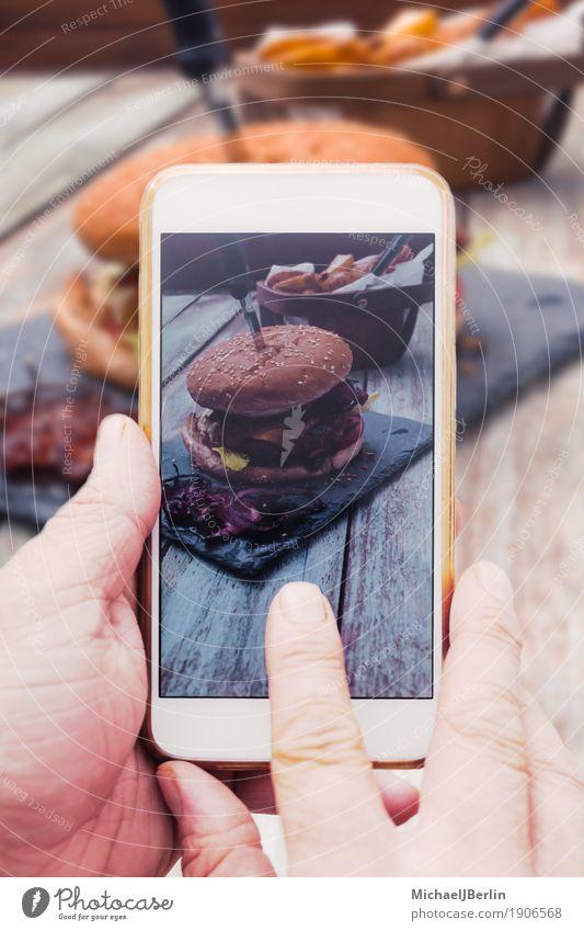 Hand mit Smartphone Handy, Foto von Burger auf Tisch Lebensmittel Fleisch Brot Brötchen Cheeseburger Speck soziale medien teilen Internet Telefon PDA Holz