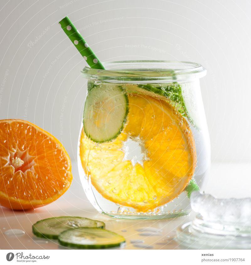 Kühles Erfrischungsgetränk mit Mineralwasser, Mandarine, Gurkenscheiben, Eiswürfel und grünem Trinkhalm Getränk trinken Trinkwasser Glas Gesundheit