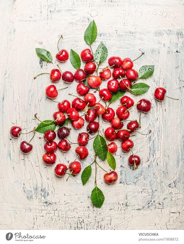 Zerstreute Kirschen mit grünen Blättern Lebensmittel Frucht Ernährung Bioprodukte Vegetarische Ernährung Stil Design Gesundheit Gesunde Ernährung Sommer Tisch