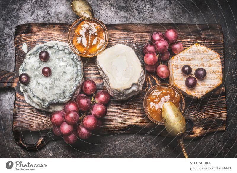 Rustikale Käseplatte mit verschiedenen Käse Lebensmittel Frucht Ernährung Getränk Stil Design Restaurant gelb Brie Feinschmecker Snack altehrwürdig