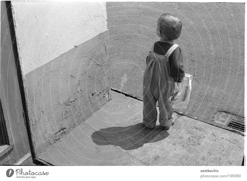 Kind Sommer Tür warten stehen Wege & Pfade Kleinkind Mensch Bürgersteig Tasche Tüte tragen Ausgang Plastiktüte anhaben gebeugt