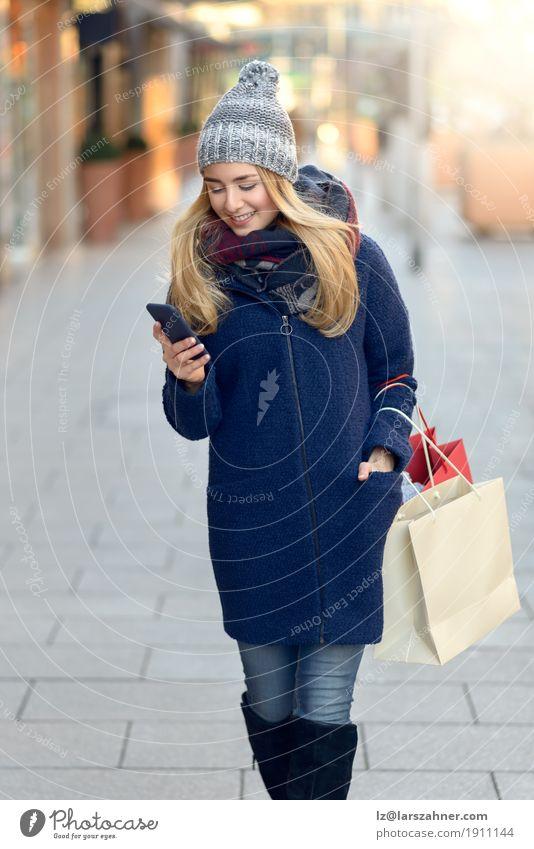 Moderne junge Frau beschäftigt mit ihrem Handy Lifestyle schön lesen Winter Telefon PDA Technik & Technologie Erwachsene 1 Mensch 18-30 Jahre Jugendliche Stadt