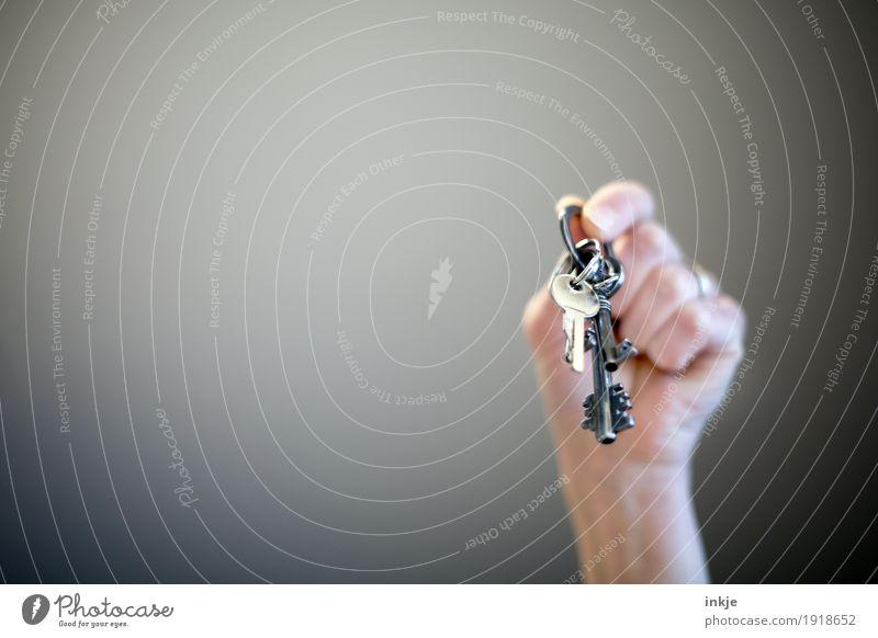 Torwächter und Schlüsselmeister. Hand Fundstück festhalten hängen geheimnisvoll hochhalten finden Vor hellem Hintergrund Vignettierung Farbfoto Innenaufnahme
