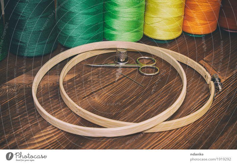 farbiger Faden in den Spulen mit hölzernen Bändern für Stickerei Design Tisch Industrie Handwerk Schere Platz Mode Bekleidung Holz braun gelb grün orange rot