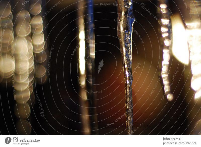 zapfenduster Wasser Winter Eis Frost Schnee leuchten Flüssigkeit kalt Kitsch schön braun gelb schwarz geheimnisvoll Vergänglichkeit Eiszapfen glänzend Licht