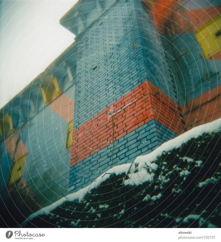 Bunter Bunker Haus Bauwerk Gebäude Architektur Mauer Wand Fassade blau gelb rot Schutz Hecke Schnee Winter Light Leak Farbfoto mehrfarbig Außenaufnahme Holga