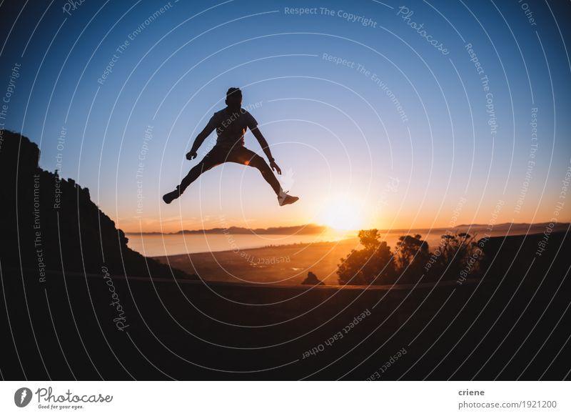Schattenbild des netten jungen Mannes, der hoch in Sonnenuntergang springt Lifestyle Freude Wohlgefühl Tourismus Ausflug Abenteuer Freiheit Sommer Junger Mann