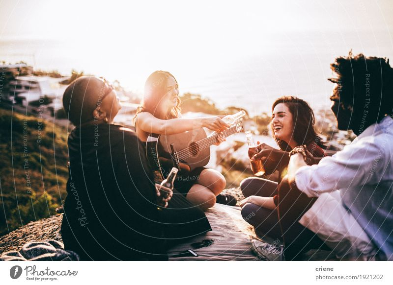 Gruppe Freunde, die Getränke genießen und Gitarre spielen Freude Erwachsene sprechen Lifestyle lachen Menschengruppe Zusammensein Freundschaft Musik