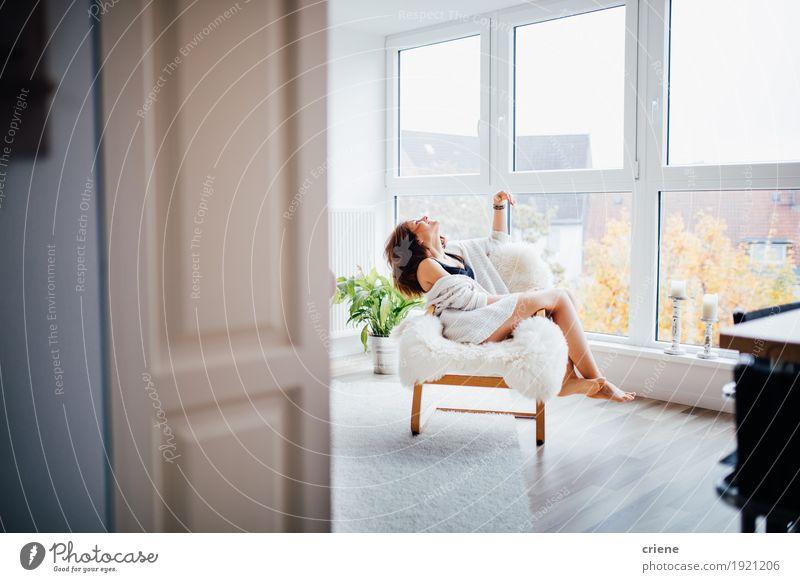 Junge kaukasische Frauen, die sich zu Hause genießen Lifestyle Freude Glück Wohlgefühl Erholung Häusliches Leben Wohnung Innenarchitektur Möbel Sofa Stuhl Raum