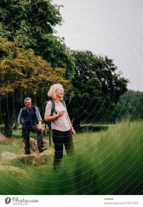 Glückliche ältere Paare auf grünen Feldern einer Wanderungabflussrinne Mensch Frau Natur Mann Freude Lifestyle Wege & Pfade Sport lachen Tourismus Zusammensein