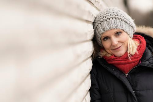 Rotschälchen / Graukäppchen Junge Frau Jugendliche Erwachsene Gesicht 1 Mensch 30-45 Jahre Mauer Wand Mantel Schal Mütze blond Lächeln Blick schön Farbfoto
