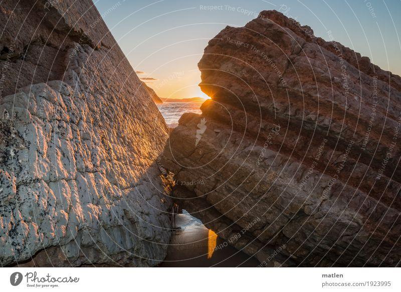 Blinzel Umwelt Natur Landschaft Wasser Himmel Wolkenloser Himmel Horizont Sonne Sonnenlicht Schönes Wetter Felsen Küste Strand Meer exotisch blau braun grau