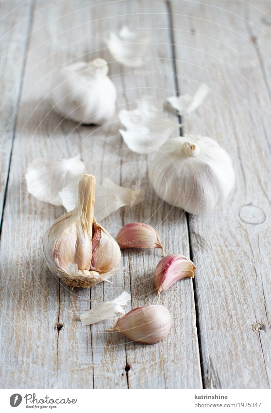 Organischer Knoblauch auf dem alten Holztisch Gemüse Kräuter & Gewürze Vegetarische Ernährung Tisch frisch grau weiß Verfall Knolle Gewürznelke Lebensmittel