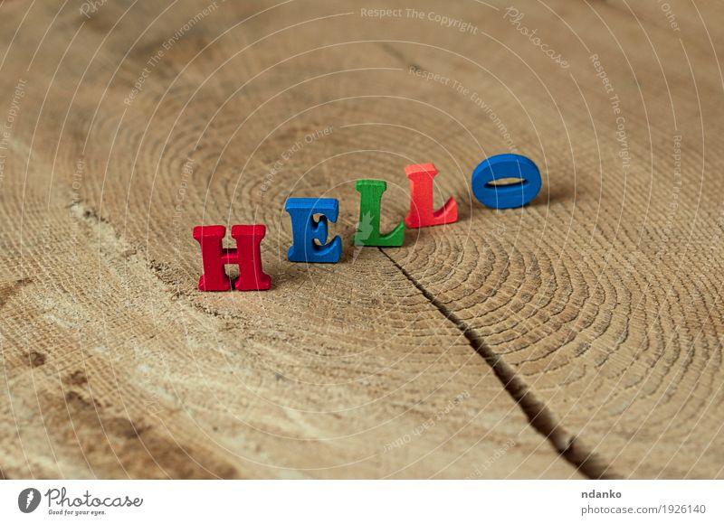 Wort hallo von den kleinen hölzernen Buchstaben auf einem Stumpf blau grün rot sprechen Holz Schule braun orange Kommunizieren Idee Spielzeug Text