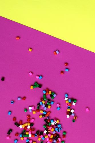 farbige Perlen auf Fucsia und gelbem Hintergrund Ferien & Urlaub & Reisen Freude Leben Innenarchitektur Lifestyle Hintergrundbild Feste & Feiern Design