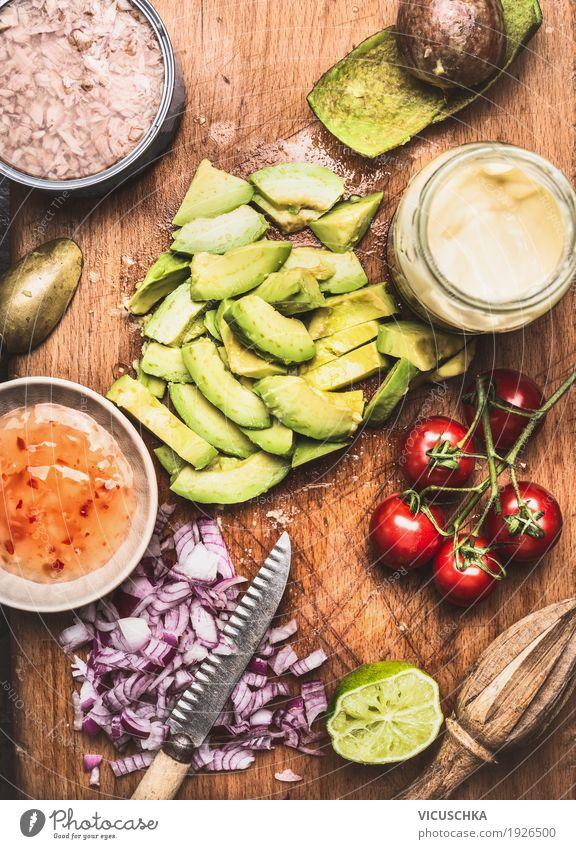 Geschnittene Avocado mit Messer und Kochzutaten Lebensmittel Gemüse Salat Salatbeilage Kräuter & Gewürze Öl Ernährung Mittagessen Büffet Brunch Bioprodukte