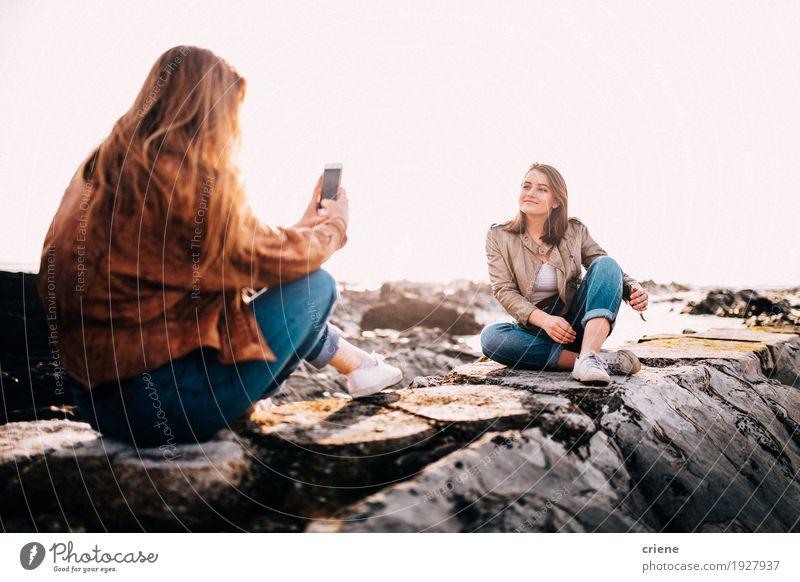 Mensch Frau Jugendliche Junge Frau Meer Wolken Freude Strand Erwachsene Lifestyle feminin Felsen Zusammensein Freundschaft sitzen Technik & Technologie