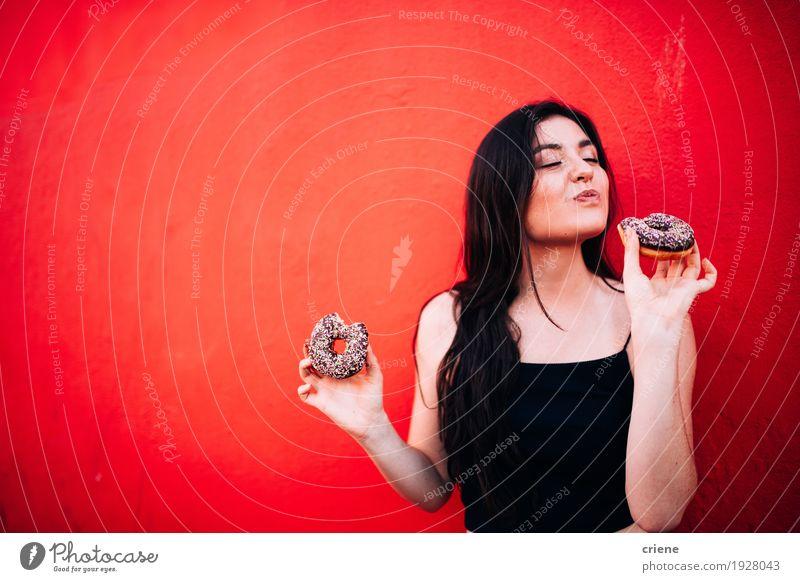 Junges glückliches kaukasisches Mädchen, das Schokoladenschaumgummiringe isst Lebensmittel Kuchen Dessert Süßwaren Essen Diät Fastfood Lifestyle Freude Mensch