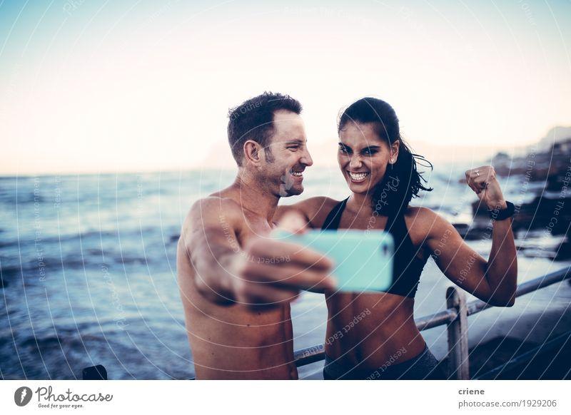 junge Sportler paar unter Selfie mit Smartphone Jugendliche Junge Frau Junger Mann Meer Freude Strand Lifestyle Paar Zusammensein Wellen Fröhlichkeit Fitness