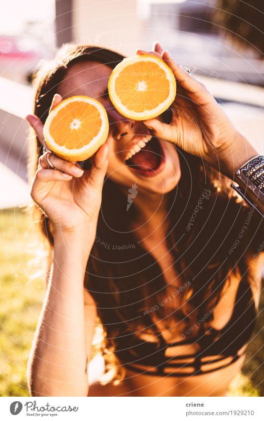 Junge Frauen, die Orangen vor ihrem Gesicht halten Lebensmittel Frucht Lifestyle Freude Erholung Sommer Sommerurlaub Sonne Sonnenbad Garten feminin Jugendliche